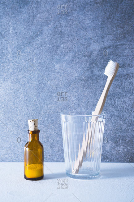 Wooden toothbrush and little bottle with toothpowder in bathroom