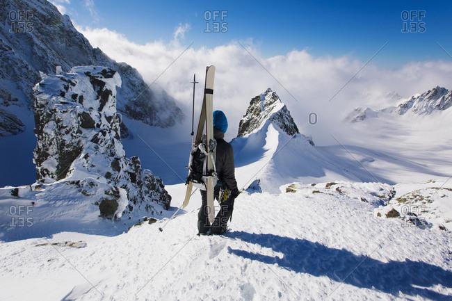Man going down mountain through snow, South Island, New Zealand