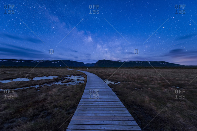 Milky Way at blue hour over boardwalk on hiking trail to Western Brook Pond in Gros Morne National Park