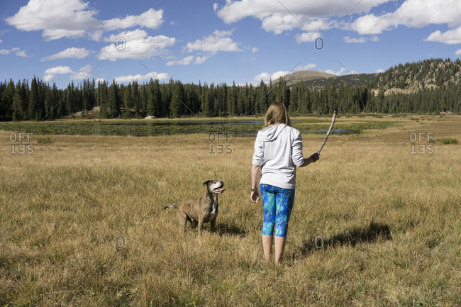 Young female plays fetch with her dog in a Colorado meadow