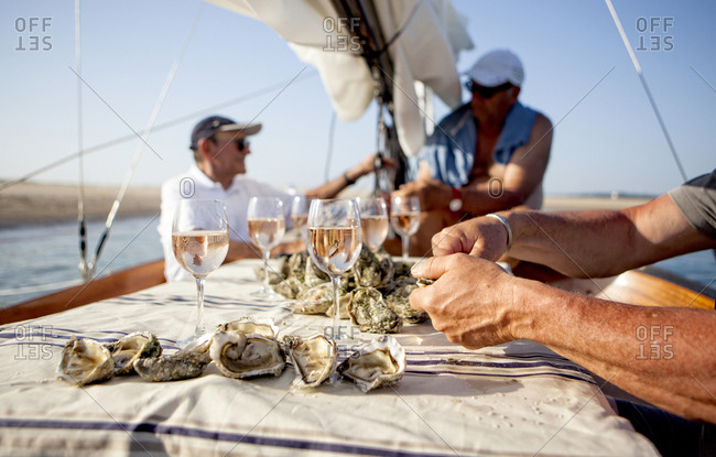 Three men having oyster and wine tasting onboard sailboat, Banc d'Arguin, Arcachon Bay, France