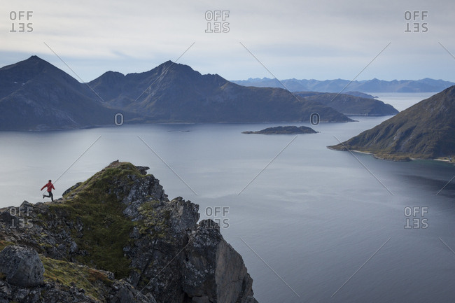 Scenery with fjords and person running towards cliff, Tromso, Troms, Norway