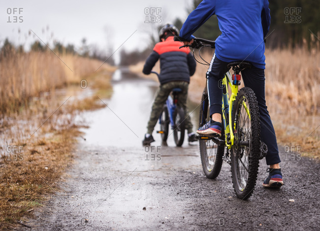 Cropped image of two boys on bikes going to ride through a puddle.