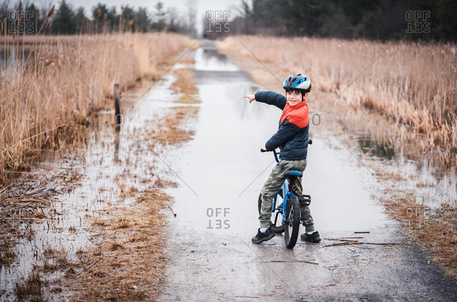 Young boy on a bike pointing to a flooded section of biking trail.