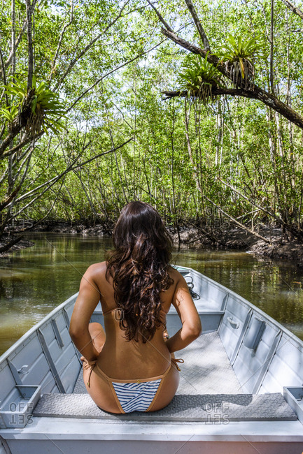 Woman riding boat to Cleandro Waterfall, South Bahia state, Brazil