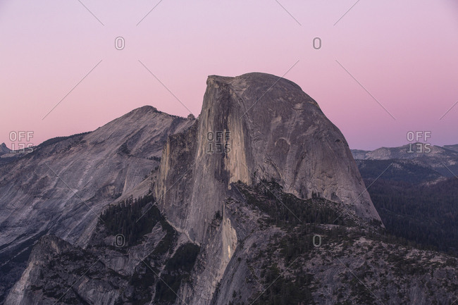 Half dome rock glowing purple and pink at sunset
