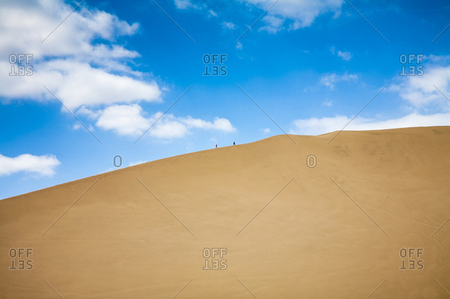 Two people walking up a large sand dune above Huacachina, Peru
