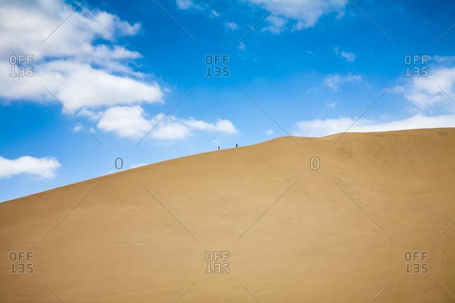 Two people walking up a large sand dune above Huacachina, Peru