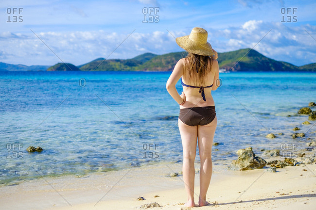 Woman on tropical beach looking at blue water