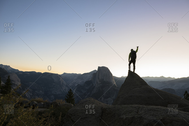 Man standing on a rock with Half Dome in background at sunrise. Yosemite, CA, USA.