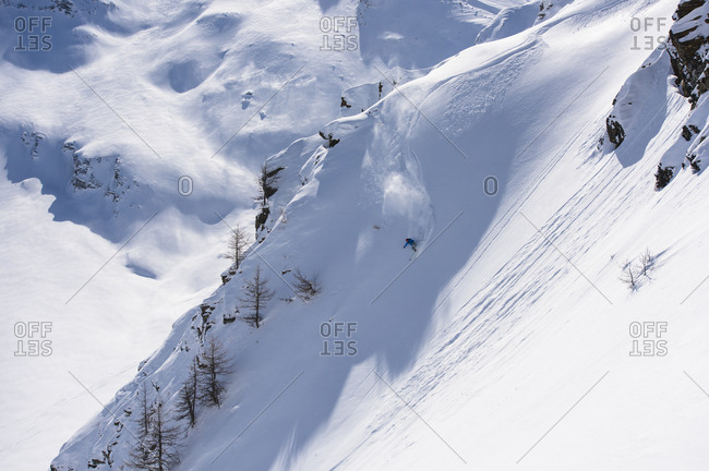 Person backcountry skiing down snowy mountain slope in Swiss Alps, Simplon Pass, Valais Canton, Switzerland