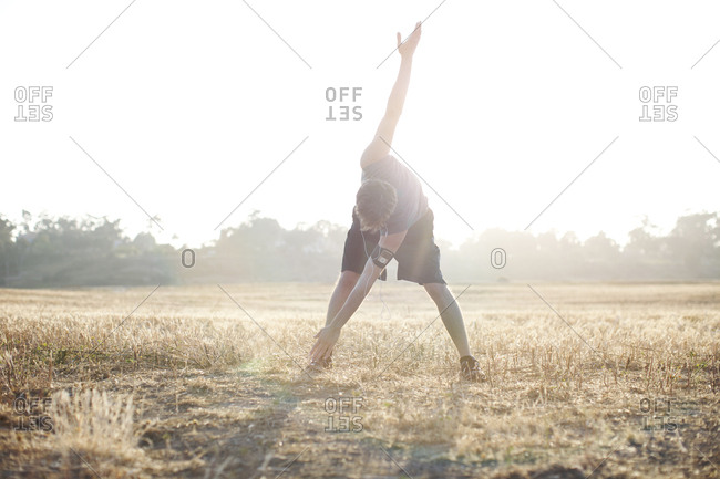 Man in his late 20's stretching before running it an open field in San Diego, California.