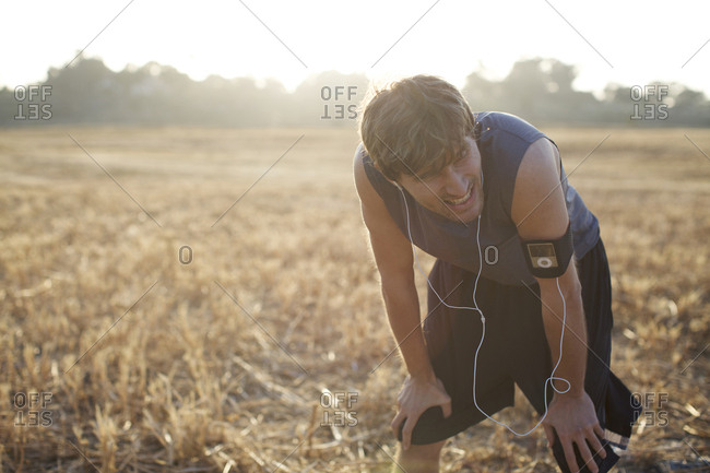 Male runner in his late 20's catches his breath as he finishes his run it an open field in San Diego, California.