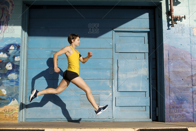 Woman runs and leaps in front of a big blue door in San Diego, California.