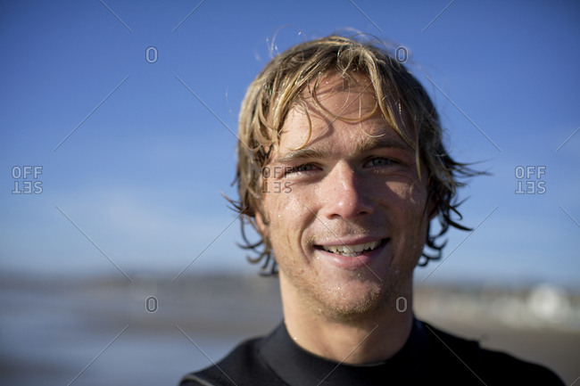Young male surfer at Pacific Beach in San Diego, California on a sunny day smiles and look straight at the camera.