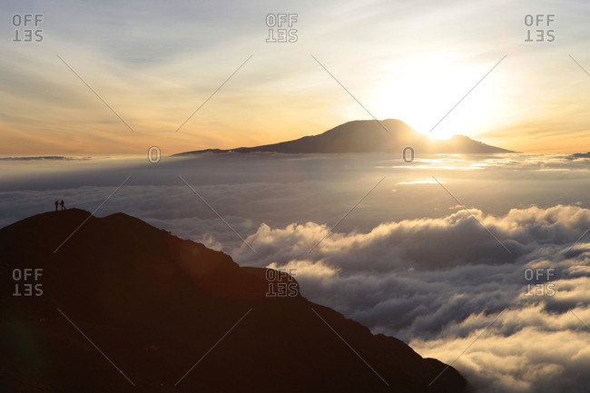Two hikers near the summit of Mount Meru, a trekking mountain in Africa. In the background is Mount Kilimanjaro.
