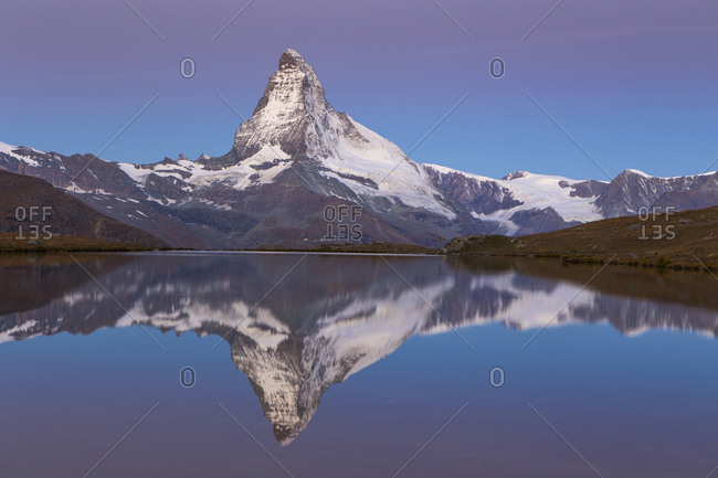 The famous Matterhorn is reflected in the Stellisee mountain lake early morning when turning pink purple by the first sunlight.