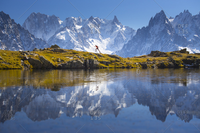 A young male runner is sprinting over a mountain ridge near Chamonix with the spectacular Mont Blanc range in the background.