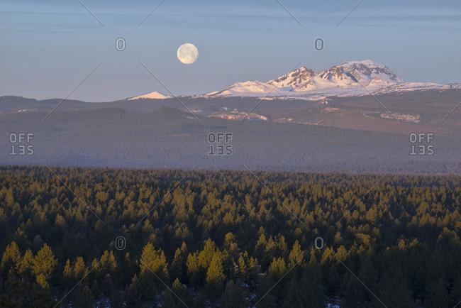Moon setting over Broken Top Mountain at dawn