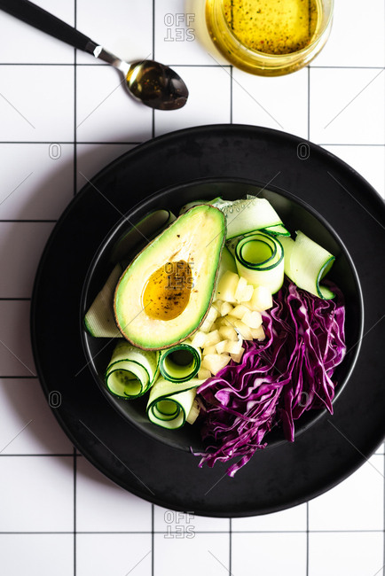 Vegan avocado salad in black bowl on grid background