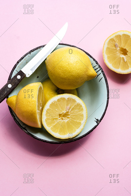 Lemons in bowl on pink background