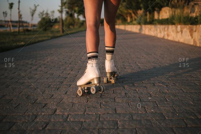 Legs of woman skating away wearing roller skates