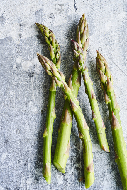 A close-up of five asparagus spears on a surface.