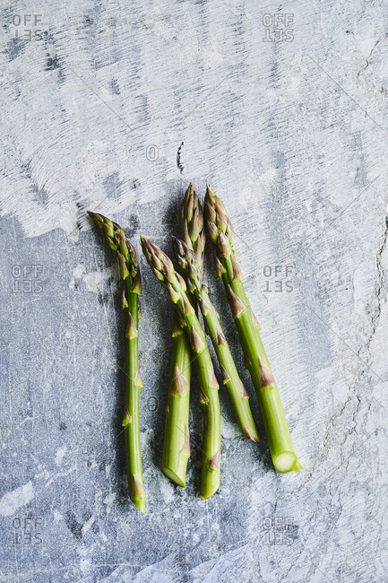 Five asparagus spears on a surface.