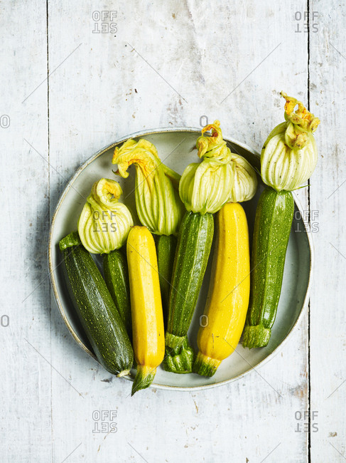 Fresh green and yellow courgettes in a bowl with flowers.