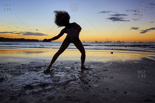 Silhouette of woman making moves on beach after sunset