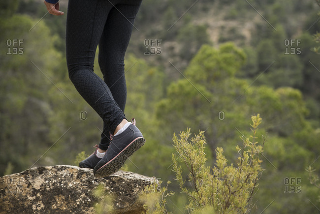female hiker pauses on a rock in the forests of Zaragoza, Spain