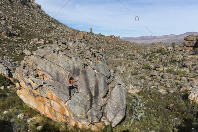 A female rock climber climbs high on a boulder in the Cederberg Mountains of South Africa