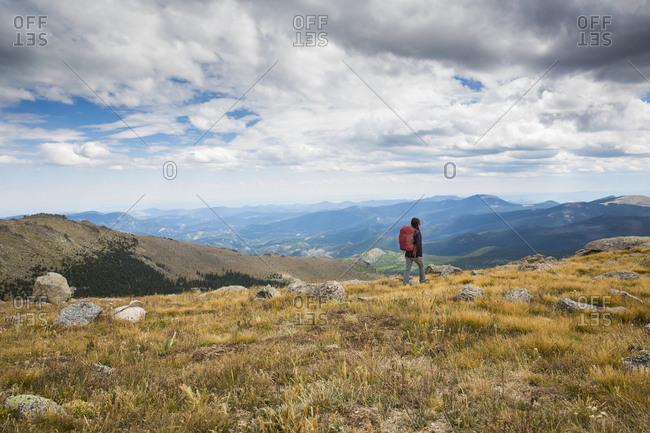 A Woman Walks Across A Field Towards The Mountains In Colorado