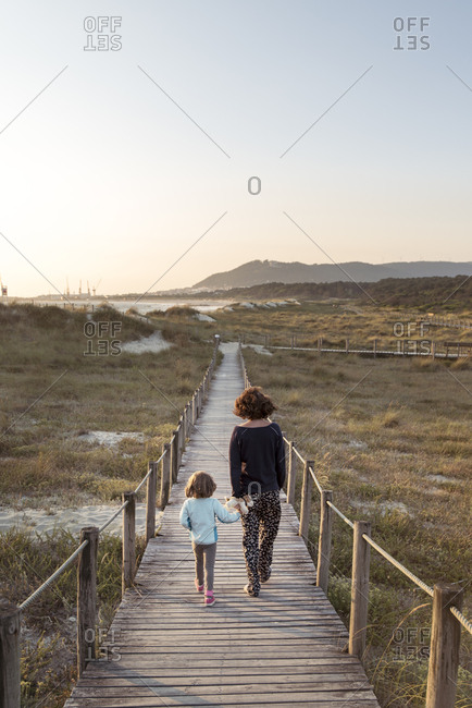 Mother and daughter walking along boardwalk, Viana do Castelo, Portugal