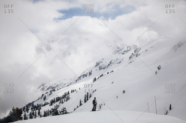 SQUAMISH, BRITISH COLUMBIA, CANADA. A female skier stops during a run down a groomed slope.