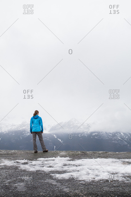SQUAMISH, BRITISH COLUMBIA, CANADA. A young woman in hiking clothes looks over a foggy, wintry view from a flat rock edge.