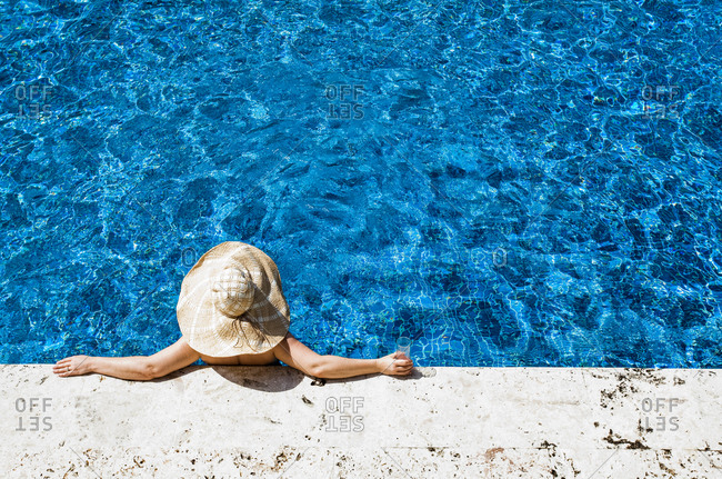 JAMAICA. A woman in a giant straw hat relaxes at the edge of a blue pool.