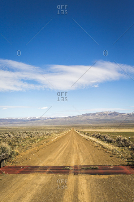HARNEY COUNTY, BURNS RANGER DISTRICT, OR, USA. A dirt road leads into a vast desert landscape of flat sage and distant mountains.