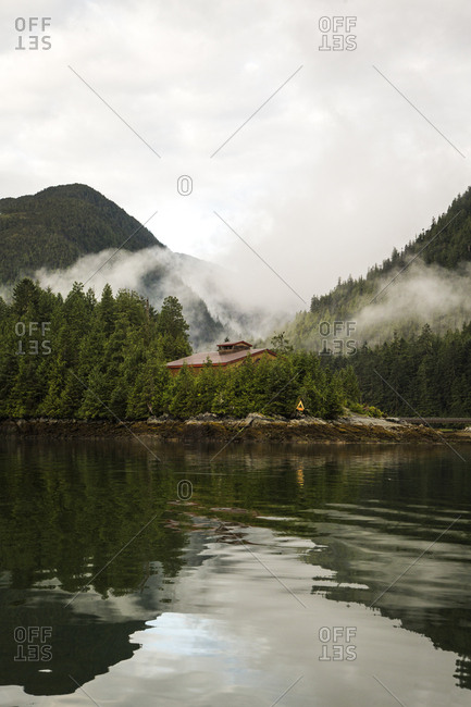 Fog Hangs Over A Roofline Of A Community Lodge In A Thickly Forested Mountain Landscape