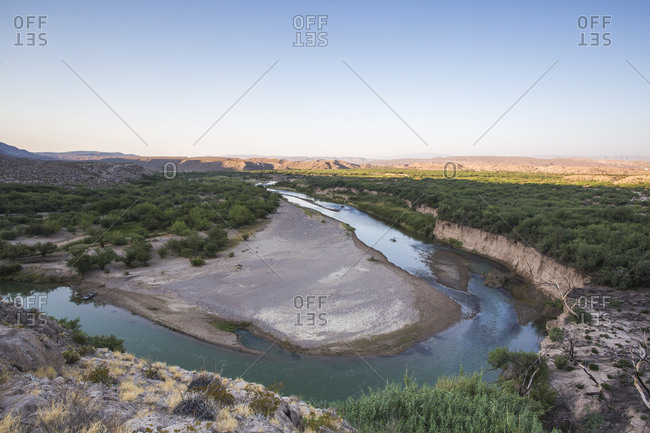 A Green River Curves Around A Deep Bend In An Arid Desert Landscape At The Border Of Us And Mexico