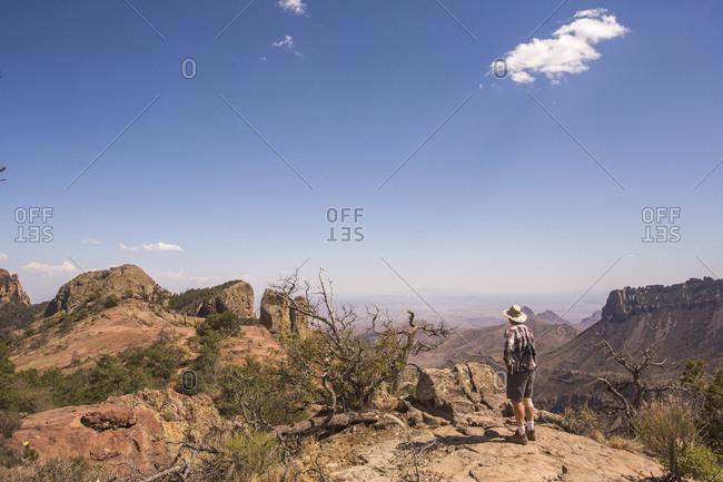 A Man Standing On A Rock Exploring Desert Landscape