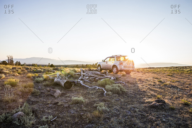 SUV car at sunrise in natural setting, Koosharem, Utah, USA