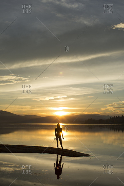 Silhouette of woman standing on shore of Lake Pend Oreille at sunset, Sandpoint, Idaho, USA