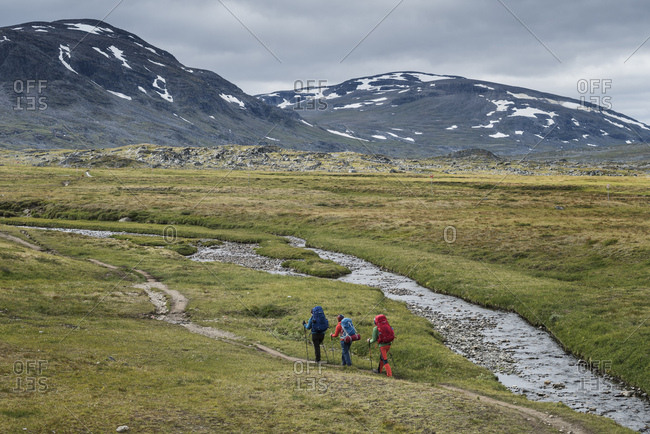Hikers walk on trail in mountain landscape between Alesjaure and , Kungsleden trail, Lapland, Sweden