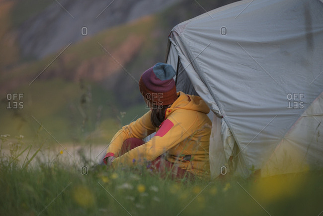 Female hiker sits outside tent surrounded by summer wildflowers