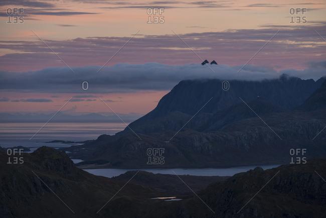 Twin peaks of Solbjorntind behind clouds at sunset