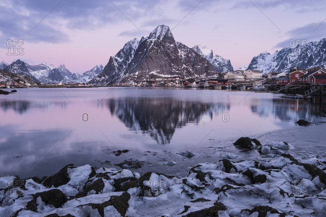 Olstind mountain peak rises over frozen shoreline in Reine, ��y, Lofoten Islands, Norway