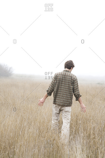 A young man walks with arms out in a field of tall grasses, California.