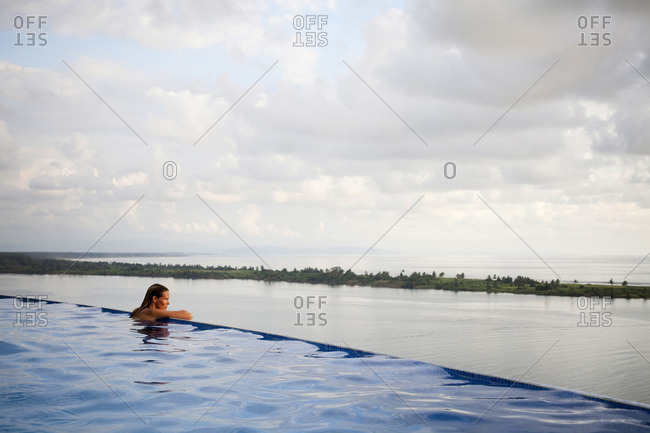 A woman sits with her arms on the edge of an infinity pool overlooking the wide open ocean.