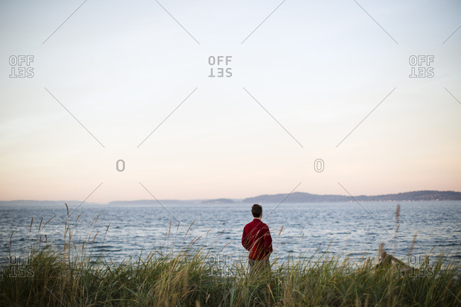 A young man stands on the beach at Discovery Park in Seattle, WA.